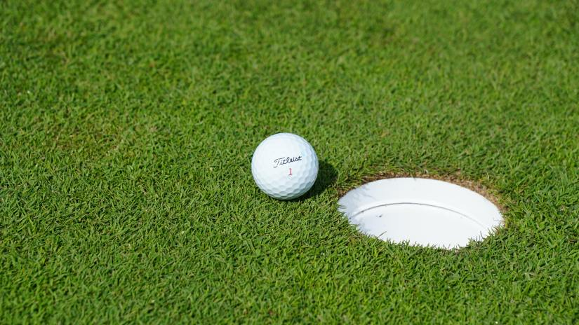 A golf ball sits on the edge of a hole on a bright green field.