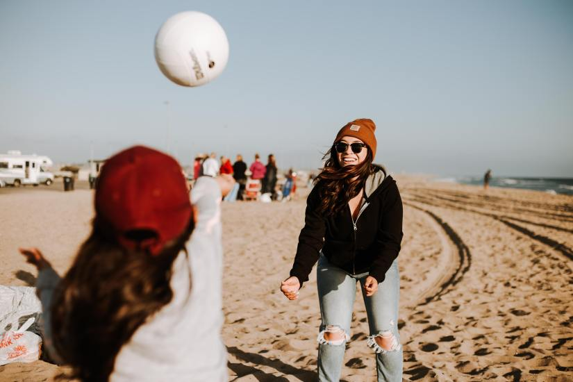 Two teen girls practice hitting a volleyball on a chilly day at the beach.