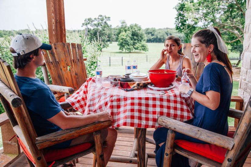 Three teen siblings sit at a table on the porch eating dinner.