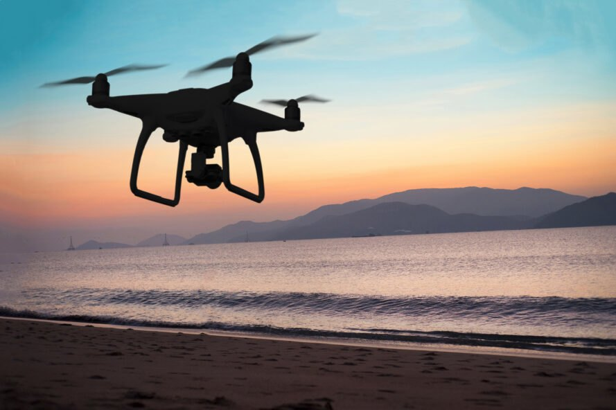 drone flying over ocean during sunset