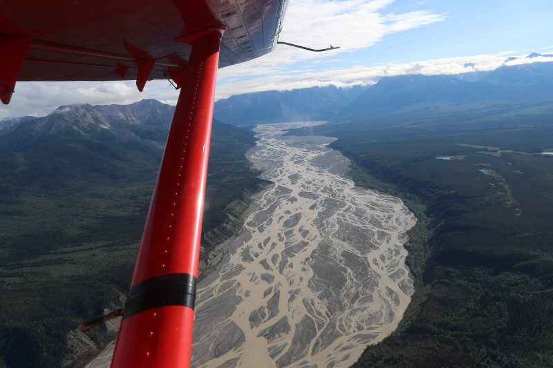 Aerial view of multiple-streamed river with airplane strut in foreground.