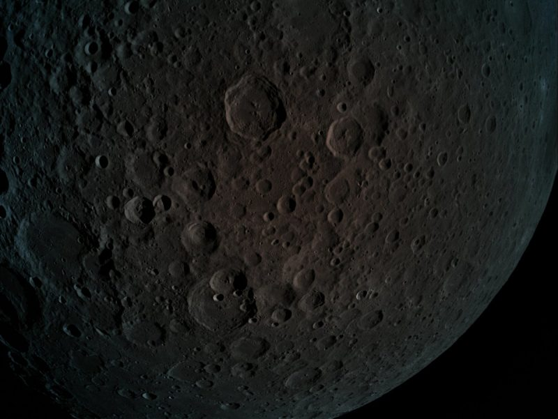 Dark gray lightly cratered moon surface.
