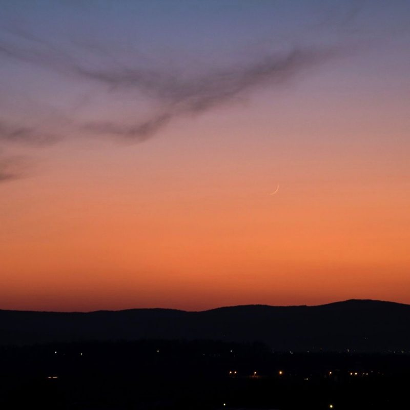 Thin young moon against an orange twilight sky.