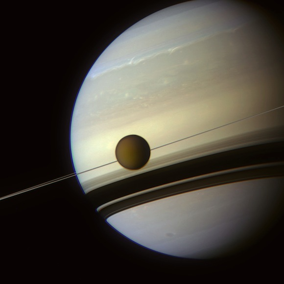 Saturn with Titan silhouetted against edge-on rings as if strung on wire.