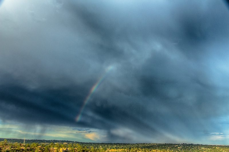 Rays converging under storm clouds to the right with a partial rainbow in the middle of the photo.
