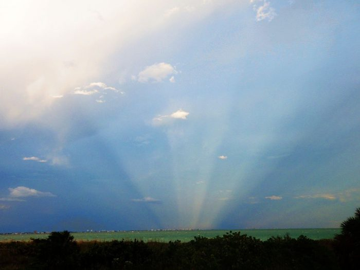 Nearly vertical rays converging to horizon beyond a green field.