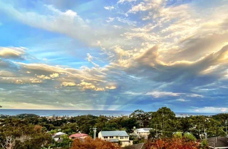 Blue sky over a town with rays emanating from the horizon.