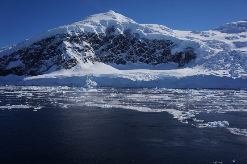 View of a glacier from the sea, with an icy mountain in the background.