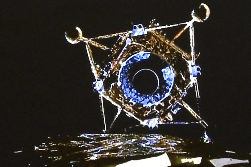 A fragile-looking lunar landing vehicle, seen from its mothership to be descending.