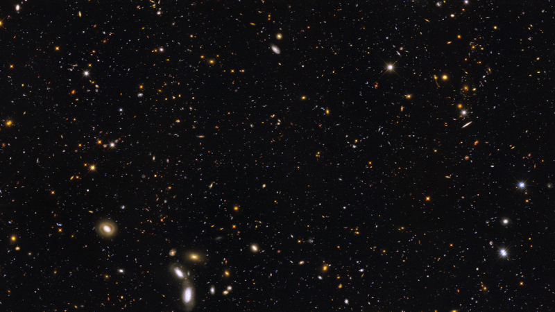 Multicoloured speckles and tiny ovals (galaxies) on a black background.