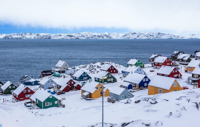 Snow-covered seaside town with 25 small, multicolored houses.