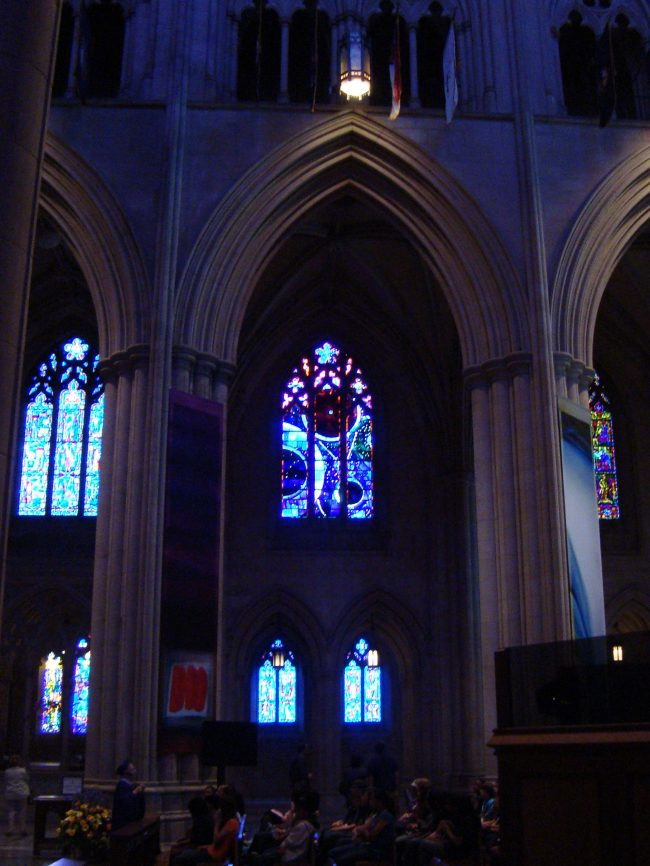 A darkened cathedral with giant columns and stained-glass windows inside tall Gothic arches.