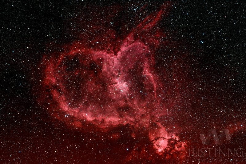 Gas nebula with reddish heart outline and bright core.