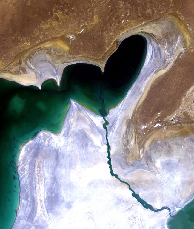 A dark-green lake shaped like a heart on brown and white ground.