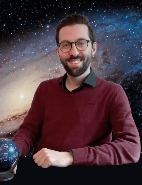 Bearded man with glasses, holding celestial globe, in front of Andromeda galaxy mural.