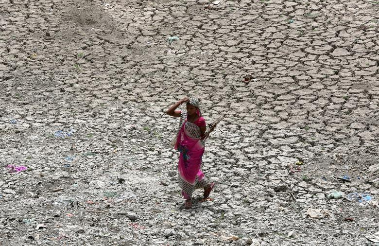 A women carries firewood as she walks through a dried-up portion of the Sabarmati river on a hot summer day in Ahmedabad, India, May 16, 2018.
