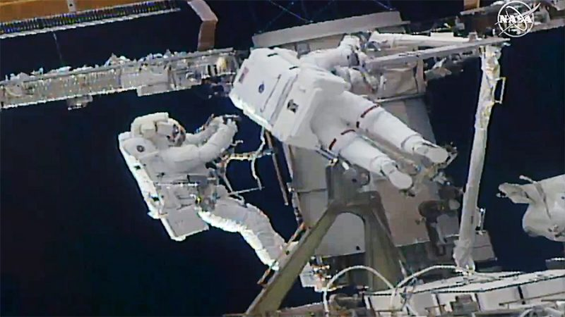 Two astronauts in white spacesuits working on white metal, black background.