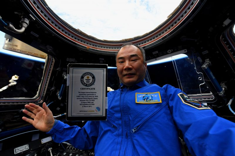Gray-haired man in blue inside ISS with floating plaque in front of him.