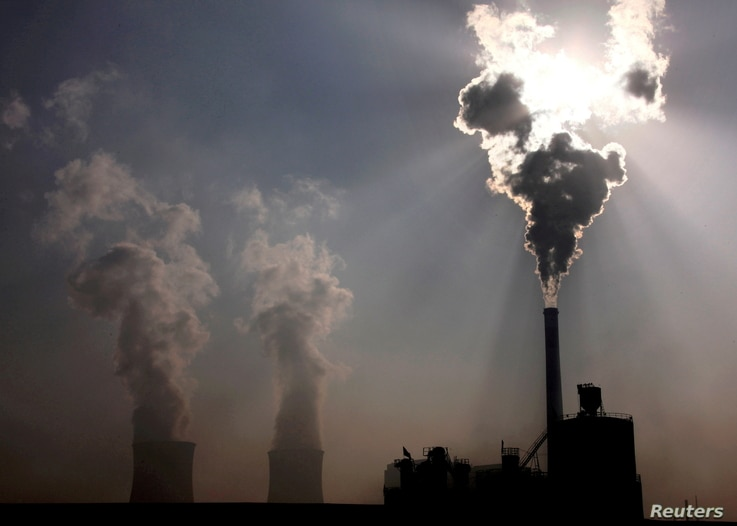 FILE PHOTO: A coal-burning power plant can be seen behind a factory in China's Inner Mongolia Autonomous Region, October 31,…