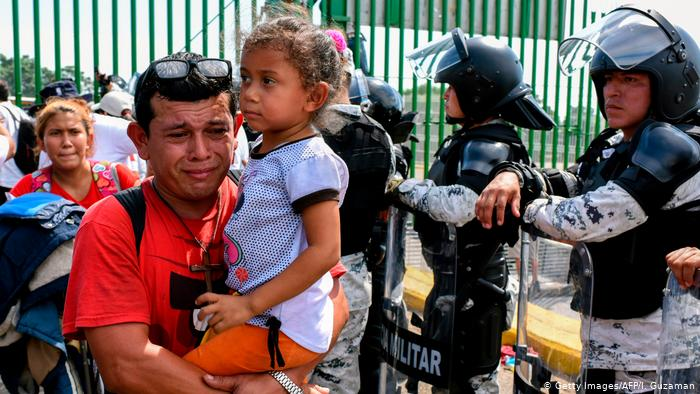 An upset-looking man holds his daughter. Armed riot police stand guard in the background.