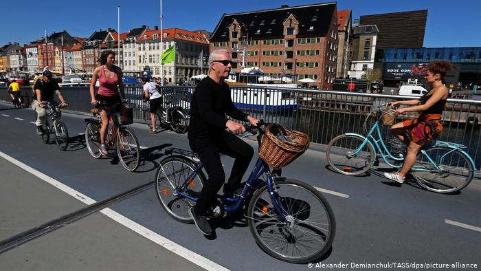 People ride bicycles on a road in Copenhagen