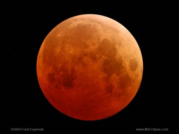 A total lunar eclipse shown as a reddish, dark orange moon.