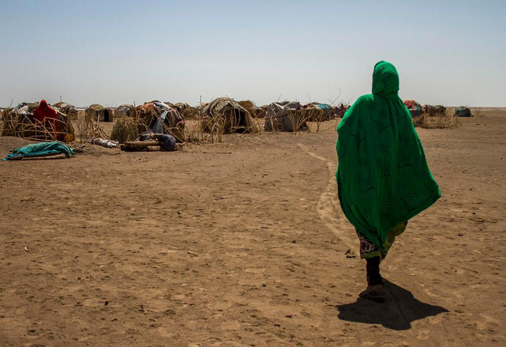 A woman looks into the distance at the temporary shelter in a refugee camp in Ethiopia.