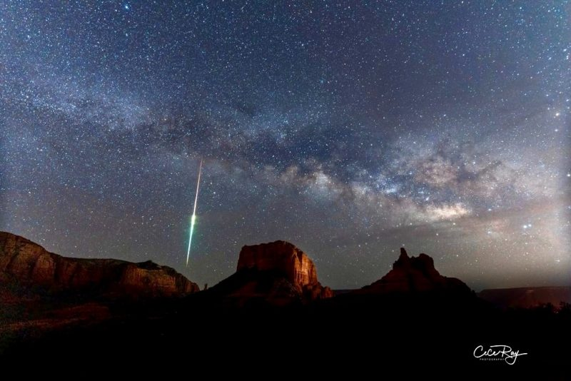 Red rock formations with star cloud and streak of light above.