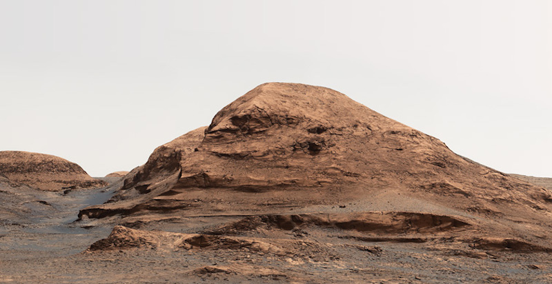 Brownish rocky hill with light-colored sky above.