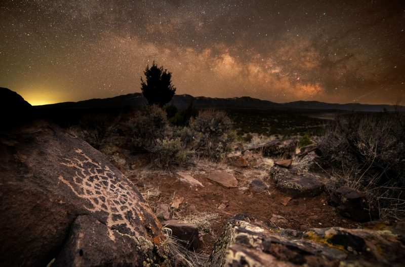 Orange-tinted starry clouds with spider-like rock etching in foreground.