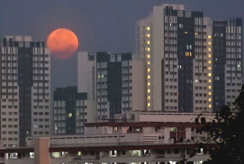 Orange orb, darker on the bottom, peeking out from between high-rise buildings.