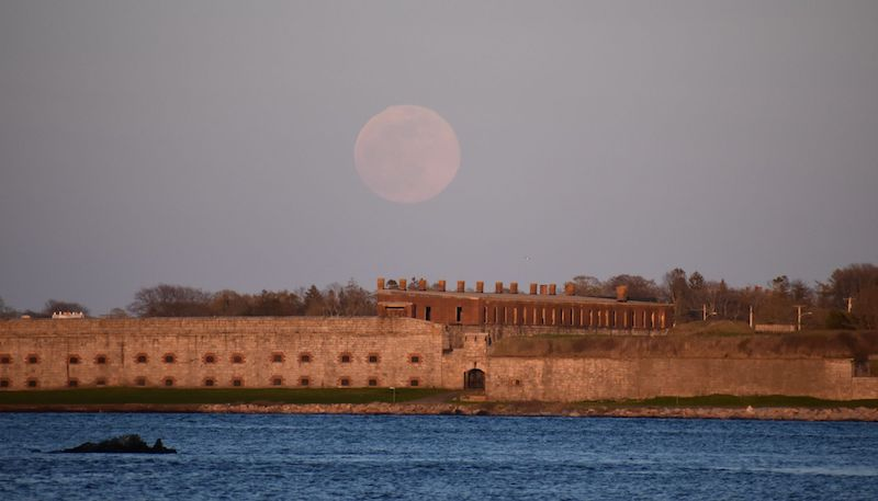 Faint pink full moon over old fort with water in the foreground.