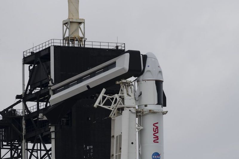 A Falcon 9 rocket and Crew Dragon spacecraft are pictured standing vertically, in position for liftoff on a cloudy morning.