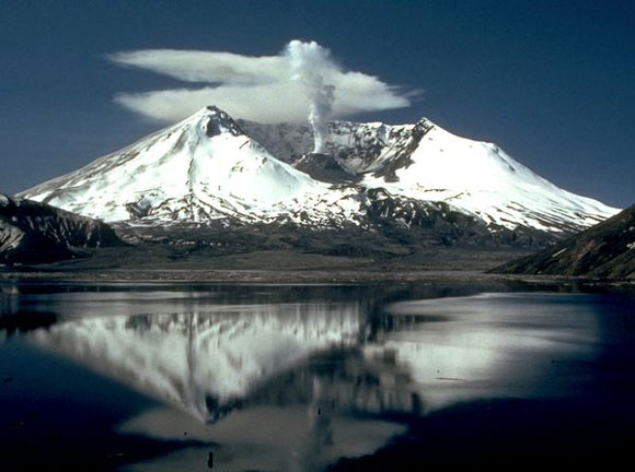 Snowcapped mountain with crater at summit, smoke plume from the center, clouds behind and a reflection in the foreground water.