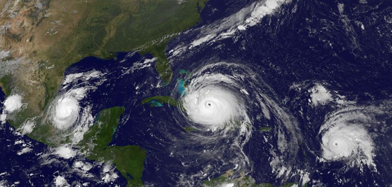 Satellite image of 3 hurricanes in the Allantic ocean with North America to left.