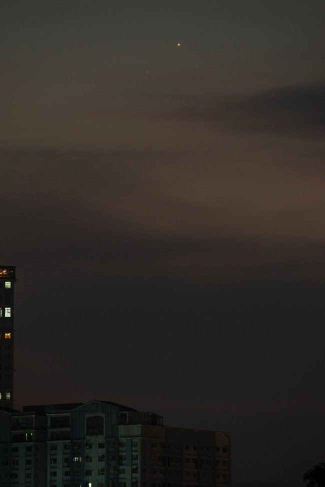 Venus-Mercury above a rooftop, in a city.