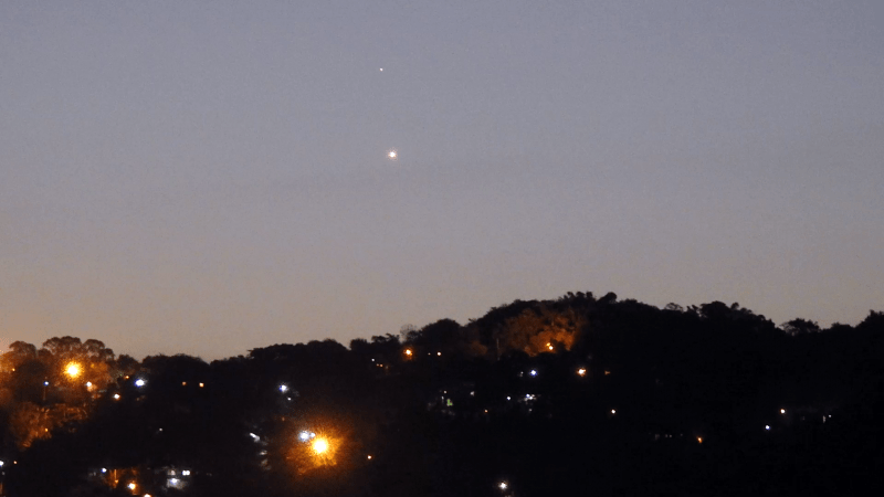 Mercury-Venus above a wooded hill with scattered house and street lights.