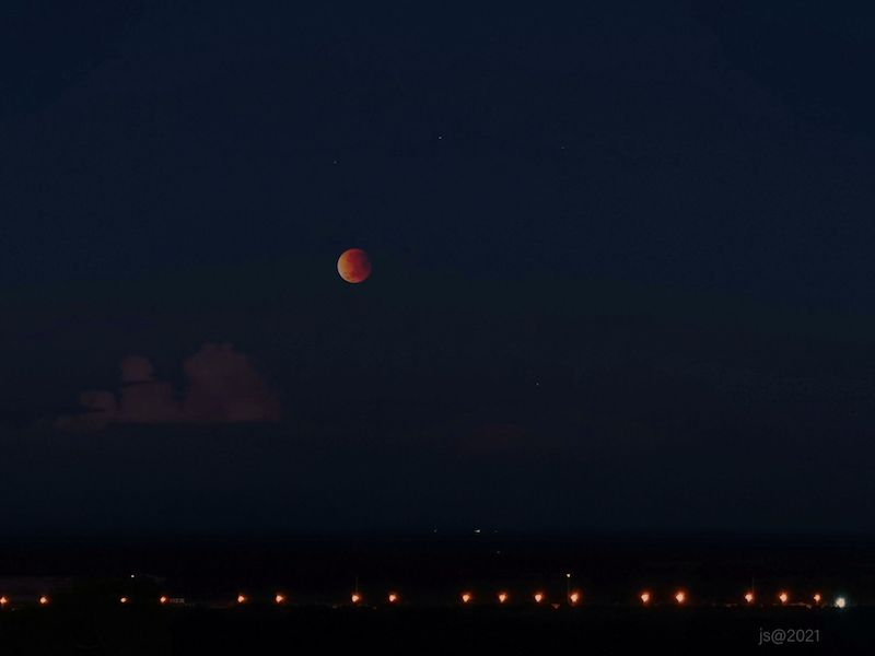 Lunar eclipse: shining orange and white moon on a black sky background.