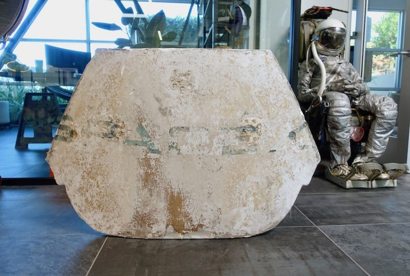 A hexagonal white panel is displayed, battered and worn, with the writing SpaceX faintly visible.