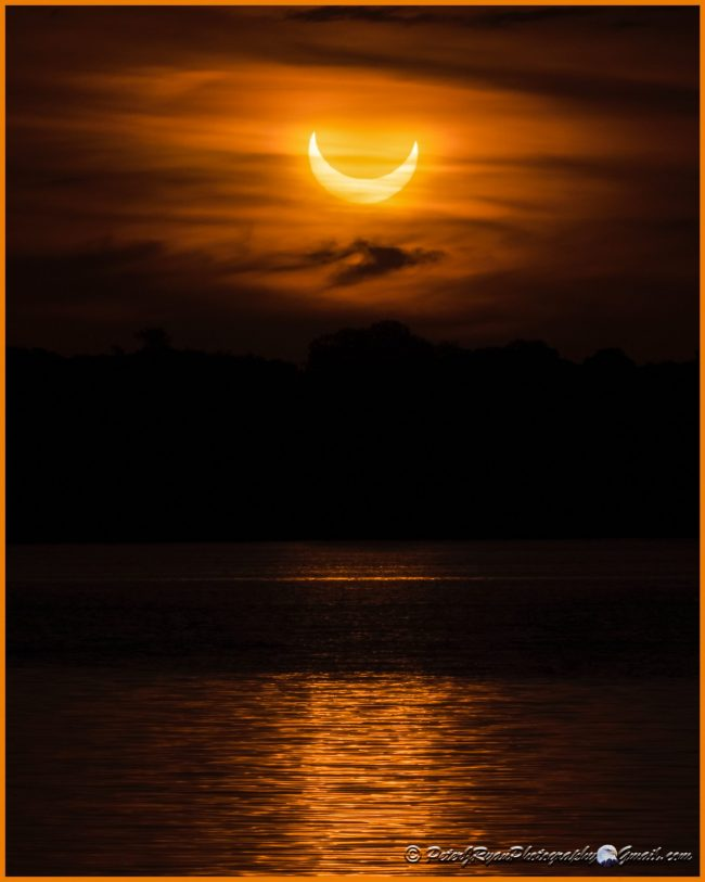 Solar eclipse glowing through clouds over water.