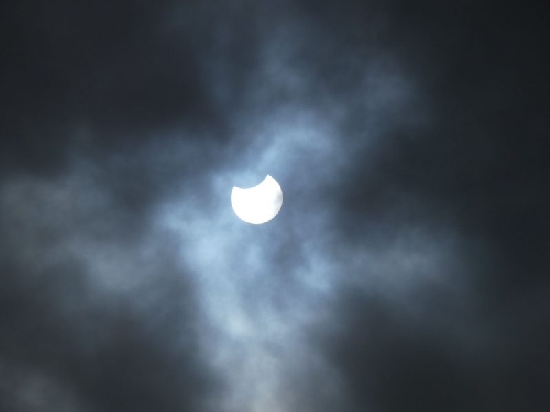 Clouds with white sun peering out and small dark piece missing.