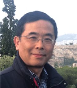 Lightly smiling man with black hair and glasses in front of scenic view.