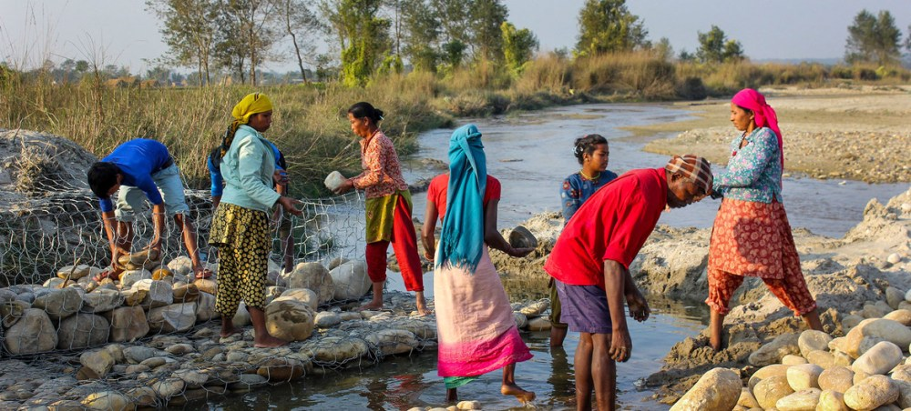 Women build barriers in Nepal to prevent the river from overflowing and flooding nearby villages.