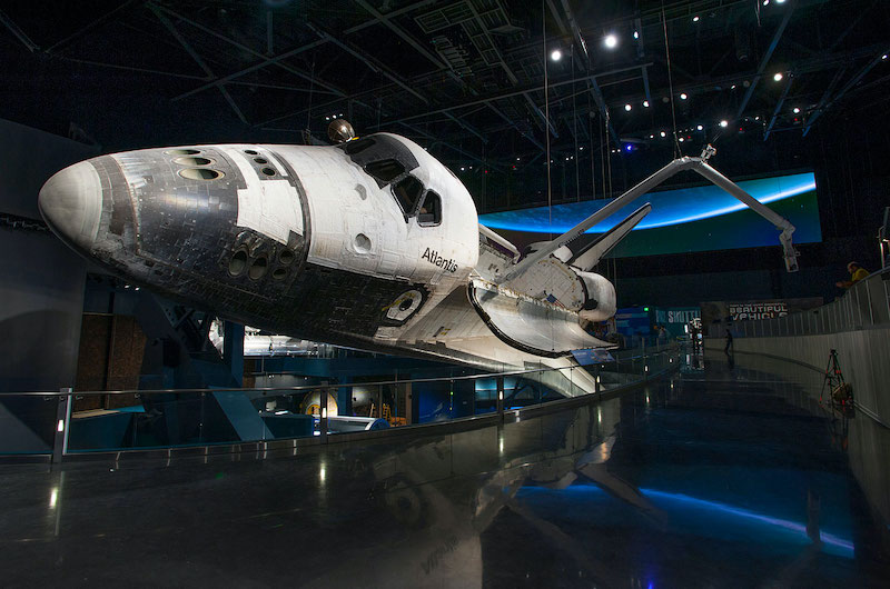 Final shuttle mission featured white space shuttle Atlantis, now on display. Image shows a black-tipped nose in a dark room with the glow of a blue Earth displayed behind it.