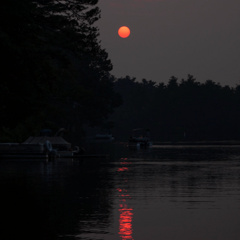 A very red sunset in a dark sky, with the sunset reflecting on a lake.