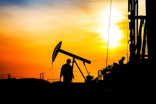 Silhouetted workers on an oil field at sundown.
