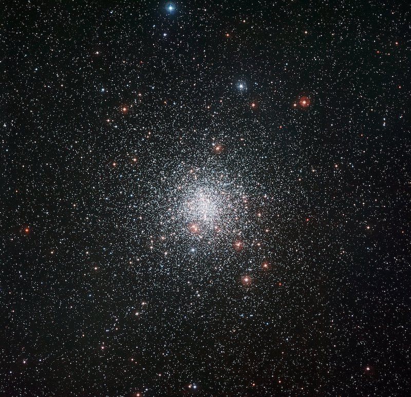 A tight cluster of faint stars, mostly white, in a dense star field with some yellow and red stars.