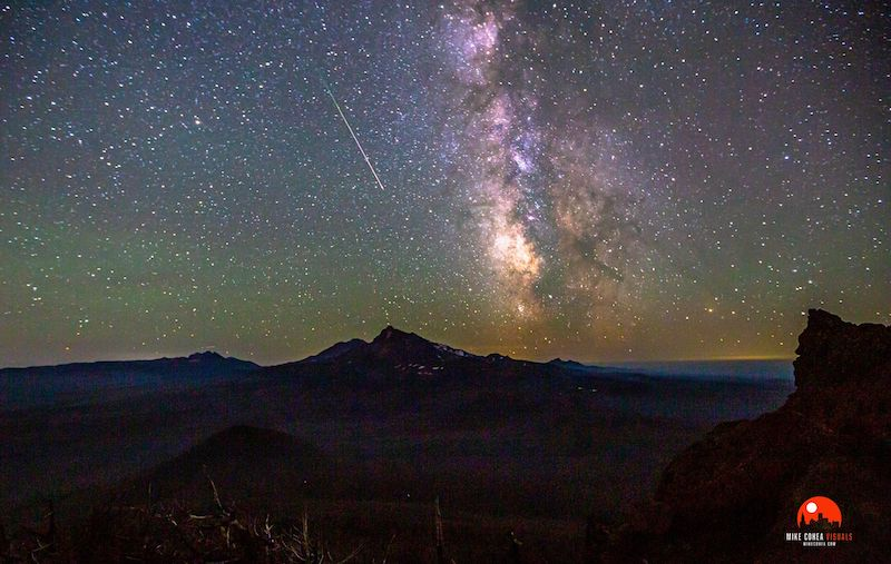 Perseid photos: A green and purple sky is freckled with white dots and a white streak across the middle.
