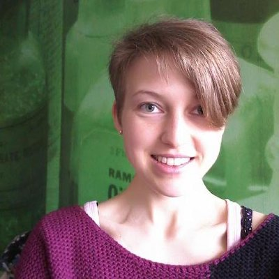 Smiling woman with short hair cut to hang down on one side of her face.