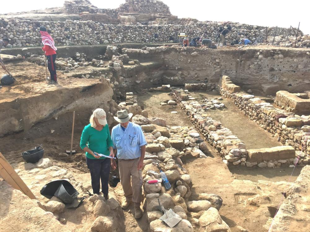 Archaeologists stand in midst of many short stone walls - the ruins of a city.